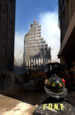 [September 13, 2001: A New York City firefighter looks up at what remains of the South Tower.]